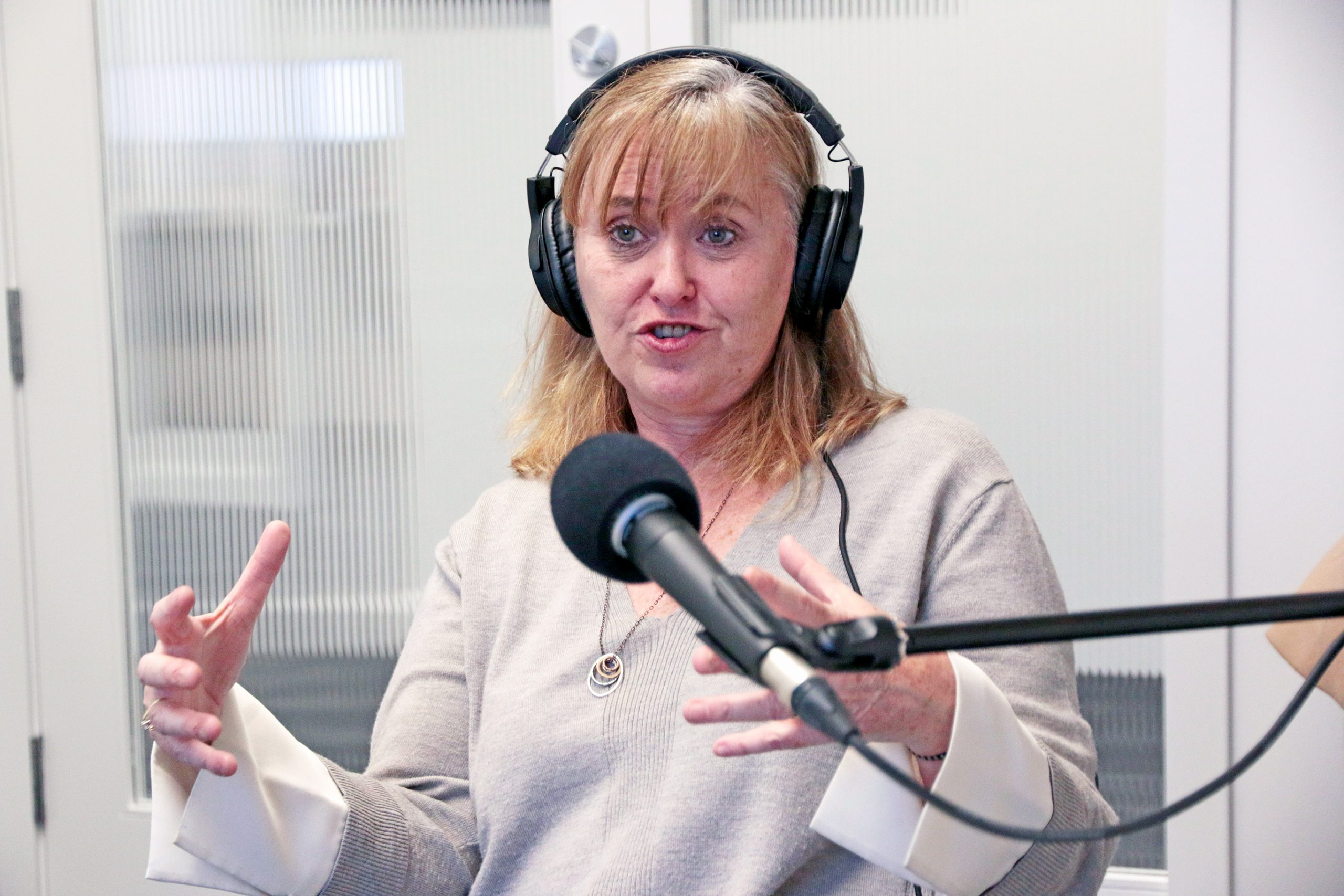 Leslie Howatt from Errors and Omissions Insurance Corporation talking in front of a microphone during the BCREA podcast recording