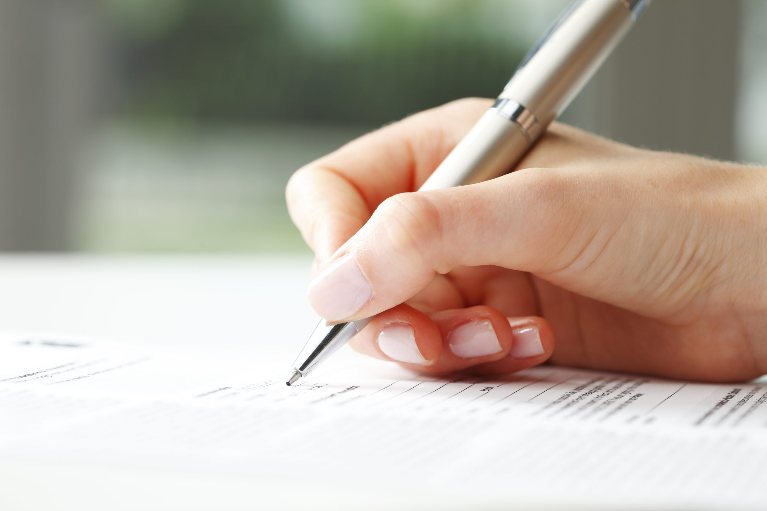 A female hand signing a document